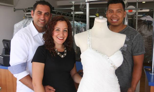 In this July 28, 2014 photo,  Michael, left, and Nicole Pagliaro pose with her wedding dress at the South Beach Dry Cleaners with owner Hector Pacheco in the Staten Island borough of New York where Nicole Pagliaro discovered the shop displaying her dress long after assuming it had been lost to Superstorm Sandy. The shop she brought it to for cleaning was destroyed by the storm, but two weeks ago Pagliaro took a different route to work and spotted it in the window of the dry cleaner's new store. (AP Photo/Staten Island Advance, Hilton Flores)
