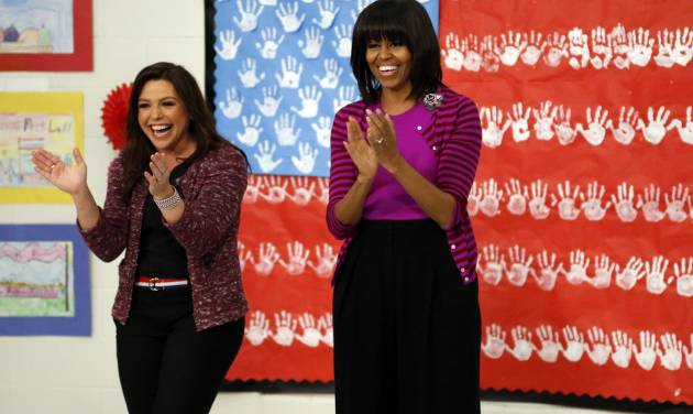 """First lady Michelle Obama and Food Network chef Rachel Ray greet students at a """"Let's Move!"""" program at the Eastside and Northside Elementary Schools in Clinton, Miss., Wednesday, Feb. 27, 2013. Obama and Ray visited with the children and conducted a cooking contest between the schools chefs. (AP Photo/Rogelio V. Solis)"""