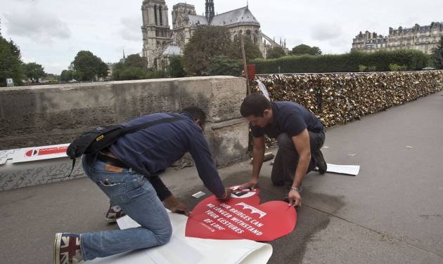 Municipality workers fix a giant sticker on the sidewalk of the Pont de l'Archeveche in Paris, Wednesday, Aug. 13, 2014. Paris is hoping to persuade visiting couples to end the recent and unwelcome tradition of fixing padlocks to the Pont de l'Archeveche. With giant stickers in three languages in French, English and Spanish. Paris began its 'Lovewithoutlocks' campaign, saying the city's famed bridge could not withstand the thousands of padlocks that cling to every available surface. (AP Photo/Michel Euler)