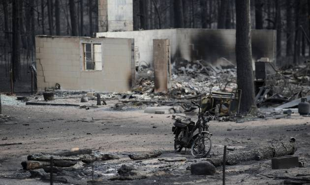 The remains of a motorcycle stands among the ruins of a home along Holmes Road Thursday, June 13, 2013, during the third day of the Black Forest Fire north of Colorado Springs, Colo. (AP Photo/The Gazette, Christian Murdock) MAGS OUT