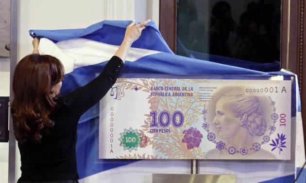 "FILE - In this July 25, 2012 photo, Argentina's President Cristina Fernandez unveils an archetype of the new 100 Argentine pesos bill bearing the profile of former late first lady Maria Eva Duarte de Peron, better known as ""Evita,"" at the government palace in Buenos Aires, Argentina. Judgment day is approaching in an epic battle between Argentina and New York billionaire Paul Singer, who has sent lawyers around the globe trying to force the South American country to pay its defaulted debts. Three U.S. appellate judges will hear oral arguments in New York on Wednesday, Feb. 27, 2013, in the case, NML Capital Ltd. v. Argentina. The case has shaken bond markets, worried bankers, lawyers and diplomats, captivated financial analysts and generated enough ""friend of the court"" briefs to kill a small forest. (AP Photo/Alberto Raggio, DyN, File)"