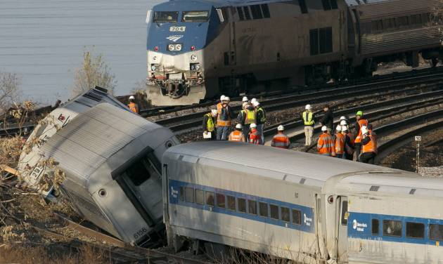 FILE - In this Dec. 1, 2013 file photo, an Amtrak train, top, traveling on an unaffected track, passes a derailed Metro North commuter train in the Bronx borough of New York. Metro North, the nation's second-largest commuter rail line said on Wednesday, June 11, 2014, it has completed most of its priorities to improve safety following a series of accidents last year. (AP Photo/Mark Lennihan, File)