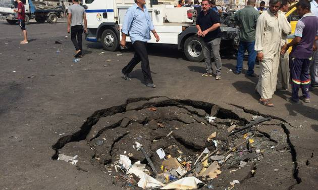 Civilians inspect a crater caused by a car bomb explosion in commercial area of New Baghdad, Iraq, Tuesday, Aug. 26, 2014. The parked car bomb exploded on Tuesday in a busy area in eastern Baghdad, killing and wounding scores of people, officials said, the latest in a series of attacks to shake the Iraqi capital as the Shiite-led government struggles to dislodge Sunni militants from areas in the country's west and north. (AP Photo/ Khalid Mohammed)