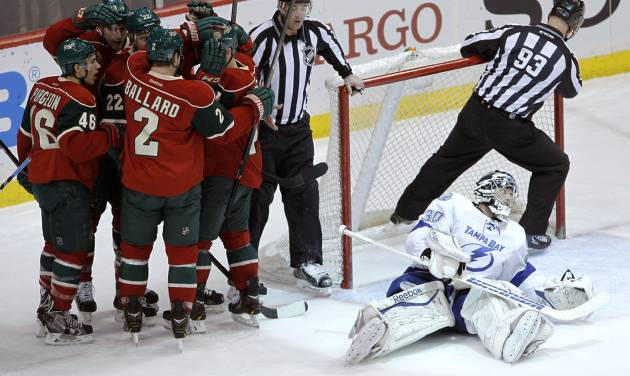 Minnesota Wild players congratulate right wing Nino Niederreiter as Tampa Bay Lightning goalie Ben Bishop, right, looks away after Niederreiter's power play goal during the first period of an NHL hockey game in St. Paul, Minn., Tuesday, Feb. 4, 2014. (AP Photo/Ann Heisenfelt)