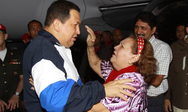 In this photo provided by Miraflores Presidential Press Office, Venezuela's President Hugo Chavez, left, embraces his mother Helena Frias as she reaches to touch his forehead as she welcomes him home at the airport in Barinas, Venezuela, Wednesday April 4, 2012. Chavez returned to Venezuela on Wednesday night after his latest round of radiation therapy treatment in Cuba. (AP Photo/Miraflores Presidential Office)