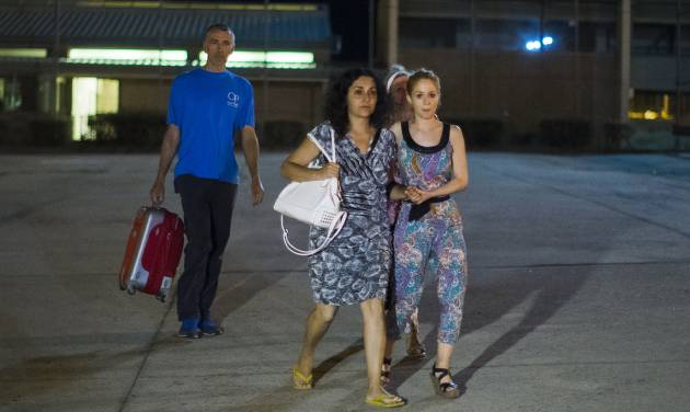 Brett and Naghemeh King, centre and left, leave Soto Del Real prison in Madrid, Spain, Tuesday, Sept. 2, 2014. British prosecutors are dropping the case against a couple who ended up in a Spanish jail after they tried to get treatment abroad for their son's severe brain tumor, authorities said Tuesday. Brett and Naghemeh King were pursued by police after they took 5-year-old Ashya out of a hospital in southern England against doctors' advice and traveled to Spain, where they planned to sell a property to pay for proton beam radiation therapy in the Czech Republic or the U.S. They were arrested on a British warrant on suspicion of cruelty to a person under 16 years of age, and are in custody in a jail near Madrid. (AP Photo/Andres Kudacki)