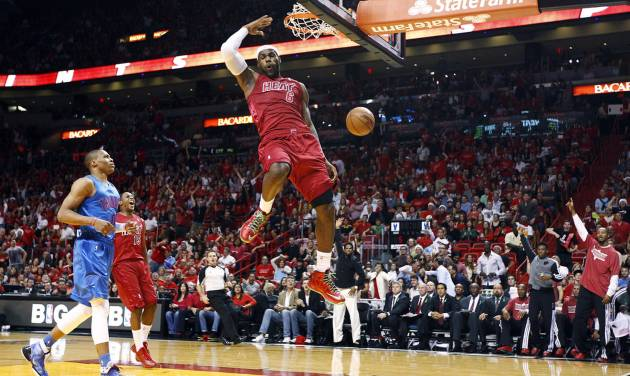 Miami Heat's LeBron James (6) dunks as Oklahoma City Thunder's Russell Westbrook (0) and Heat's Mario Chalmers (15) watch during the first half of an NBA basketball game, Tuesday, Dec. 25, 2012, in Miami. (AP Photo/J Pat Carter)