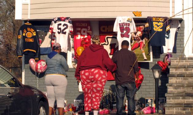 People stand by a small shrine outside the Long Island home of Kansas City Chiefs linebacker Jovan Belcher, Monday, Dec. 3, 2012, in West Babylon, N.Y. People living at and visiting the home stopped and recited a prayer at the shrine on Monday. On Saturday, Belcher killed his girlfriend and himself in Kansas City, Mo. (AP Photo/Frank Eltman)