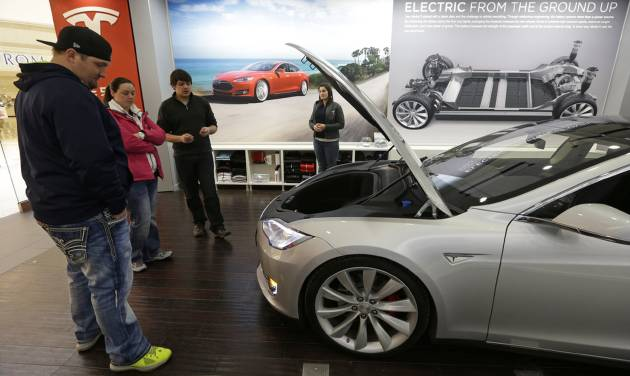 FILE - In this March 17, 2014 file photo, Robert and Sarah Reynolds, left, check out a new Tesla all electric car with Tesla representatives John Van Cleave and Raven Rivera, right, at a Tesla showroom inside the Kenwood Towne Centre in Cincinnati. The Commerce Department releases durable goods for May on Wednesday, June 25, 2014. (AP Photo/Al Behrman)