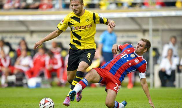 Dortmund's Ciro Immobile, left,  and Munich's Philipp Lahm vie for the ball with during the German soccer Super Cup match between Borussia Dortmund and Bayern Munich in Dortmund, Germany, Wednesday, Aug. 13, 2014. (AP Photo/Sascha Schuermann)