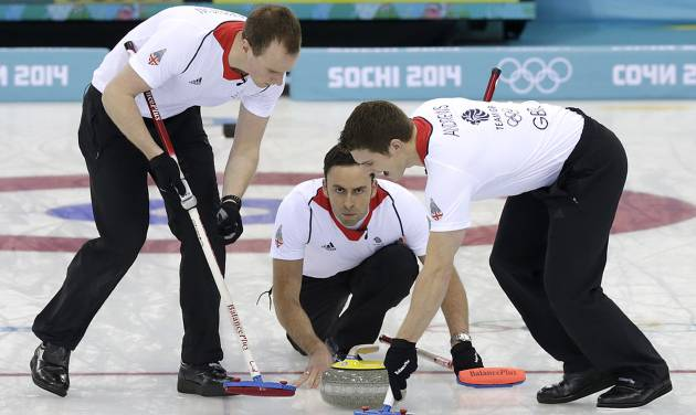 Britain's skip David Murdoch, center, delivers the rock while Michael Goodfellow, left, and Scott Andrews, sweep the ice during the men's curling gold medal game against Canada at the 2014 Winter Olympics Friday, Feb. 21, 2014, in Sochi, Russia. (AP Photo/Wong Maye-E)