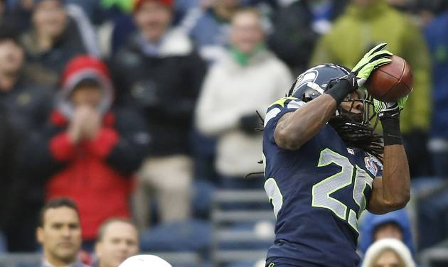 Seattle Seahawks cornerback Richard Sherman (25) intercepts a pass in front of Arizona Cardinals wide receiver Larry Fitzgerald (11) which was returned for a 19-yard touchdown during the second quarter of an NFL football game in Seattle, Sunday, Dec. 9, 2012. (AP Photo/John Froschauer)