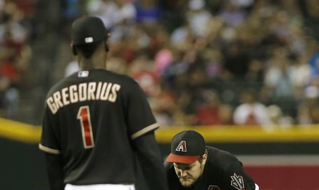Arizona Diamondbacks pitcher Wade Miley, right, rests after being hit with a line drive against the San Diego Padres during the fourth inning of a baseball game, Saturday, May 25, 2013, in Phoenix. Looking on is Didi Gregorius.  (AP Photo/Matt York)