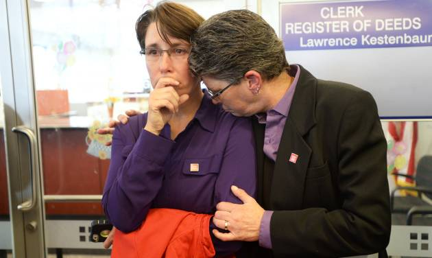 Dana Bauer, right, comforts her partner Tracy Pennington, left, after the couple learned they would not be able to apply for a marriage license at Washtenaw County Clerk's Office on Wednesday, Oct. 16, 2013, in Ann Arbor, Mich. U.S. District Judge Bernard Friedman said he won't make a decision until after hearing testimony Feb. 25 from experts on whether there is a legitimate state interest in banning gay marriage. (AP Photo/The Ann Arbor News, Melanie Maxwell)