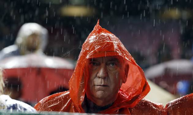A fan sits in the rain during the third inning of a baseball game between the Washington Nationals and the Los Angeles Dodgers at Nationals Park, Monday, May 5, 2014, in Washington. (AP Photo/Alex Brandon)