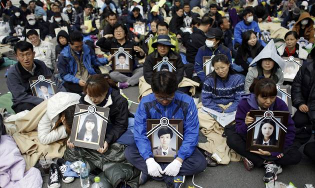 Family members holding the portraits of the victims of the sunken ferry Sewol, sit on a street near the presidential Blue House in Seoul, South Korea, Friday, May 9, 2014. Family members marched to the presidential Blue House in Seoul early Friday calling for a meeting with President Park Geun-hye but ended up sitting on streets near the presidential palace after police officers blocked them. Park's office said a senior presidential official plans to meet them later Friday. (AP Photo/Lee Jin-man)