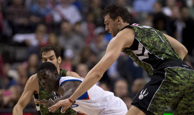 Toronto Raptors forward Andrea Bargnani, right, and Philadelphia 76ers guard Jrue Holiday chase a loose ball during first-half NBA basketball action action in Toronto, Saturday, Nov. 10, 2012. (AP Photo/The Canadian Press, Frank Gunn)