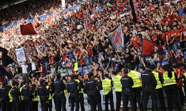 Line of policemen control Osasuna's supporters after one fence of the stadium was broken while people celebrated a goal of their team, during their last  Spanish League soccer match between Osasuna and Betis,, at El Sadar stadium, in Pamplona northern Spain, Sunday, May 18, 2014. Five people was injured. (AP Photo/Alvaro Barrientos)