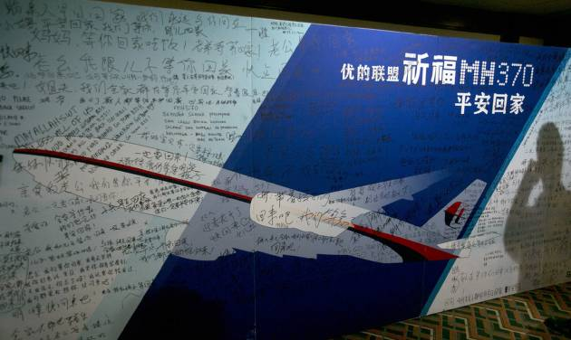 """FILE - In this March 24, 2014 file photo, the shadow of a man using his mobile phone falls on a board with the characters """"Pray for MH370 safe return"""" meant for relatives and workers to write their prayers and well wishes in a room reserved for relatives of Chinese passengers aboard the missing Malaysia Airlines flight 370 in Beijing, China. Relatives of five people on board the missing Malaysian jetliner are trying to crowd source a $5 million reward for information about what happened to the plane. The group says it """"wants to provide a substantial incentive for anyone who knows the truth to come forward."""" The Boeing 777 disappeared on March 8 while carrying 239 people from Malaysia to Beijing. (AP Photo/Ng Han Guan, File)"""