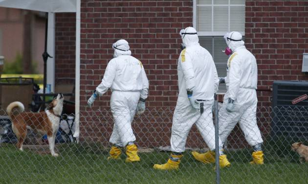 Federal agents wearing hazmat suits inspect the grounds around the house owned by Everett Dutschke, in connection with the recent ricin attacks, as one of his dogs howls Tuesday, April 23, 2013 in Tupelo, Miss. No charges have been filed against Dutschke and he hasn't been arrested. (AP Photo/Rogelio V. Solis)