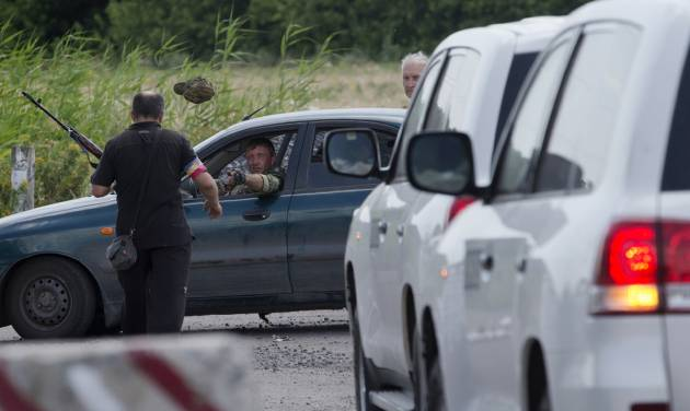 A pro-Russian rebel throws a hat to his comrade to keep uniform formality as the convoy of the OSCE mission in Ukraine approaches to a check-point near the village of Rassipne, near the scene of the Malaysia Airlines plane crash, Donetsk region, eastern Ukraine, Thursday, July 31, 2014. (AP Photo/Dmitry Lovetsky)
