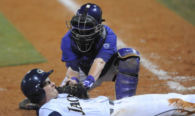 Georgia Tech's Daniel Spingola (35) is tagged out by Washington's Parker Guinn (26) trying to score on an infield ground ball to third base at the NCAA Oxford Regional at Oxford-University Stadium on Sunday, June 1, 2014. (AP Photo/Oxford Eagle, Bruce Newman)   NO SALES