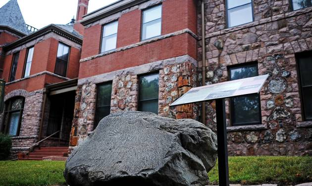 """This Wednesday, Aug. 6, 2014 photo shows a 3-ton boulder known as a """"prayer rock' on display outside the Pettigrew Home & Museum in Sioux Falls, S.D. Richard Perkins, of Sioux Falls, an artist who has had a lifelong interest in artifacts and hieroglyphics, is pushing to have the rock moved from the museum to the Crazy Horse Memorial in western South Dakota. He says the rock gets overlooked at the Pettigrew Museum and would be better placed at the memorial being built in the Black Hills to the Oglala Lakota warrior. (AP Photo/Argus Leader, Joe Ahlquist)"""