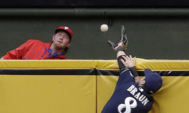Milwaukee Brewers' Ryan Braun can't catch a two-run home run hit by Philadelphia Phillies' Chase Utley during the first inning of a baseball game Monday, July 7, 2014, in Milwaukee. (AP Photo/Morry Gash)