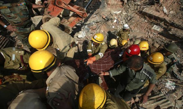 Rescue workers carry the body of a victim amid the debris of a building that collapsed in Canacona, a city about 70 kilometers (44 miles) from Goa state capital Panaji, India, Sunday, Jan. 5, 2014. A five-story building under construction in the southern Indian state of Goa collapsed on Saturday, killing at least a dozen people and leaving dozens more feared trapped under the rubble, police said. (AP Photo/Rafiq Maqbool)