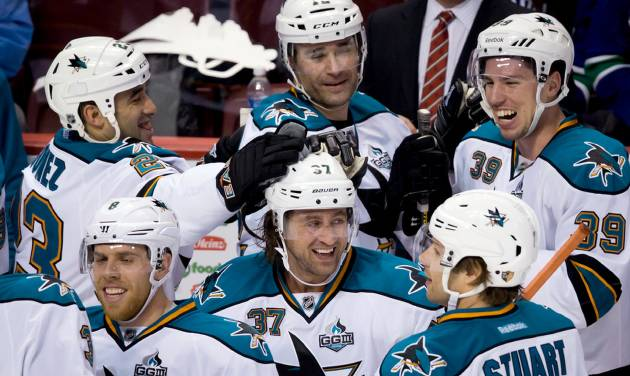 San Jose Sharks' Adam Burish, center, celebrates his goal against the Vancouver Canucks with teammates Joe Pavelski, clockwise from lower left, Scott Gomez, Patrick Marleau, Logan Couture and Brad Stuart during the second period of an NHL hockey game in Vancouver, British Columbia, Tuesday, March 5, 2013. (AP Photo/The Canadian Press, Darryl Dyck)