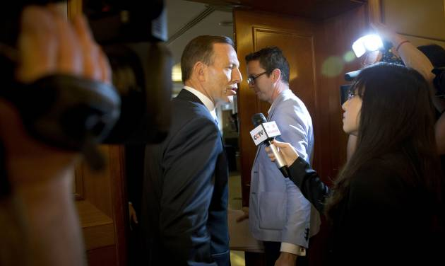 Australian Prime Minister Tony Abbott, center, is questioned by a Chinese TV reporter about the missing Malaysian Airlines Flight 370 after a press conference at a hotel in Beijing, China Saturday, April 12, 2014. With no new underwater signals detected, the search for the missing Malaysian passenger jet resumed Saturday in a race against time to find its dying black boxes five weeks after families first learned their loved ones never arrived at their destination. (AP Photo/Andy Wong)