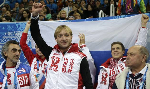 Evgeny Plyushchenko of Russia, centre, gestures after receiving his results in the men's team short program figure skating competition at the Iceberg Skating Palace during the 2014 Winter Olympics, Thursday, Feb. 6, 2014, in Sochi, Russia. (AP Photo/Darron Cummings, Pool)