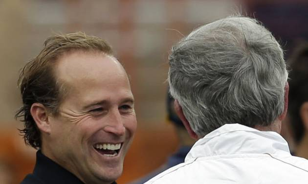 West Virginia coach Dana Holgorsen, left, talks with Texas coach Mack Brown, right, before their NCAA college football game on Saturday, Oct. 6, 2012, in Austin, Texas. (AP Photo/Eric Gay)