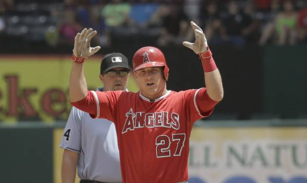 Los Angeles Angels Mike Trout reacts and gestures to towards his dugout from second base after hitting an RBI double  during the fourth inning of a baseball game against the Texas Rangers in Arlington, Texas, Sunday, July 13, 2014.  The Angels won 10-7. (AP Photo/LM Otero)