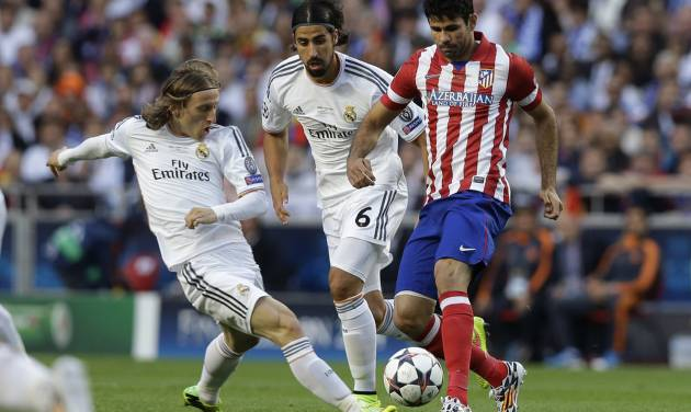 Real's Luka Modric,left and Real's Sami Khedira, centre, fight for the ball with Atletico's Diego Costa, during the Champions League final soccer match between Atletico Madrid and Real Madrid in Lisbon, Portugal, Saturday, May 24, 2014. (AP Photo/Francisco Seco)
