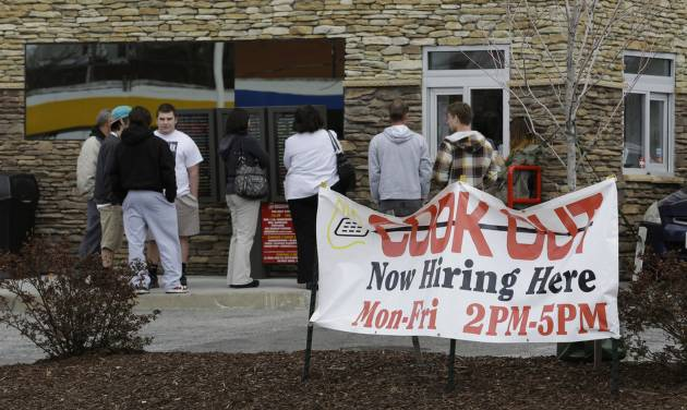 In this Friday, March 29, 2013, people line up outside a restaurant in front of a help wanted sign in Richmond, Va. The number of Americans seeking unemployment aid rose to a four-month high in the week ending March 30, 2013, although the increase partly reflects seasonal distortions around the spring holidays. The Labor Department says weekly applications increased 28,000 to a seasonally adjusted 385,000. That is the highest level since late November. The four-week average, a less volatile measure, rose to 354,250.  (AP Photo/Steve Helber)