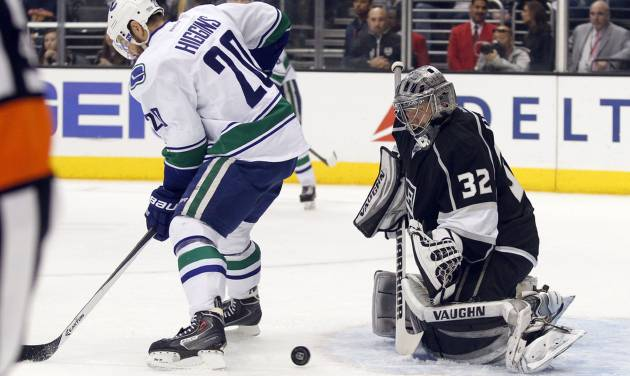Vancouver Canucks left wing Chris Higgins (20) looks for the puck on a rebound by Los Angeles Kings goalie Jonathan Quick (32) during the first period of an NHL hockey game on Saturday, Jan. 4, 2014, in Los Angeles. (AP Photo/Alex Gallardo)