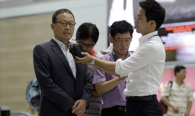 Asiana Airlines President and CEO Yoon Young-doo, left, answers reporters' questions before heading to San Francisco at the flight gate of the Incheon International Airport in Incheon, west of Seoul, South Korea, Tuesday, July 9, 2013.  A South Korean official says both U.S. and Korean investigators have been interviewing the pilots who were in the cockpit when an Asiana Airlines plane clipped a seawall before crash landing at San Francisco International Airport Saturday.(AP Photo/Lee Jin-man, Pool)
