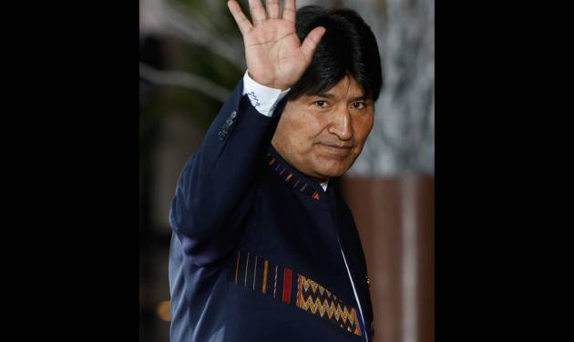 """FILE - In this Tuesday, Oct. 2, 2012, Bolivia's President Evo Morales waves to photographers upon his arrival to the Summit of South American and Arab Countries in Lima, Peru. Morales said Friday, Oct. 12, 2012, during a ceremony marking """"Decolonization Day"""" that relations with the U.S. Embassy in La Paz have become so bad they are """"like a turd."""" (AP Photo/Karel Navarro, File)"""