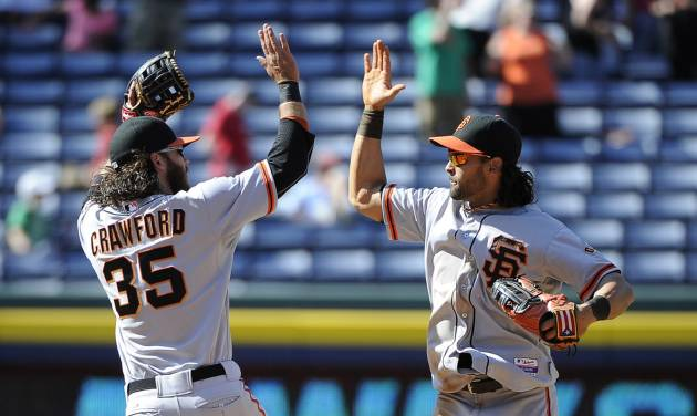 San Francisco Giants' Brandon Crawford (35) and Angel Pagan celebrate their 4-1 win over the Atlanta Braves after the ninth inning of a baseball game Sunday, May 4, 2014, in Atlanta. (AP Photo/David Tulis)