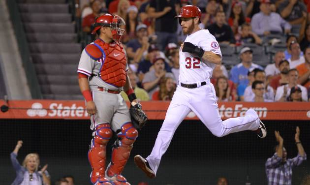 Los Angeles Angels' Josh Hamilton, right, scores on a single by Howie Kendrick as Philadelphia Phillies catcher Carlos Ruiz looks on during the sixth inning of a baseball game, Wednesday, Aug. 13, 2014, in Anaheim, Calif. (AP Photo/Mark J. Terrill)