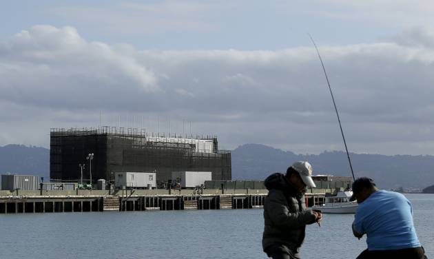 FILE - In this Tuesday, Oct. 29, 2013, file photo, two men fish in the water in front of a barge on Treasure Island in San Francisco. Google is erecting a four-story structure in the heart of the San Francisco Bay but is managing to conceal its purpose by constructing it on docked barges instead of on land, where city building permits and public plans are mandatory. Construction became obvious a few weeks ago. (AP Photo/Jeff Chiu)