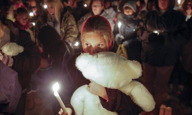 Lexi Umbarger clutches a teddy bear during a candlelight vigil in Parsons, Kan., on Wednesday, Nov. 27, 2013 for Cami Umbarger and her three young children – Hollie, Jaxon and Averie, who were found murdered in their Parsons home on Monday. David Cornell Bennett Jr. of Cherryvale was arrested on Tuesday in connection with the murders. Lexi Umbarger is the niece of Cami Umbarger and was one of nearly 200 people who turned out near the crime scene for the vigil. (AP Photo/The Wichita Eagle, Travis Heying)