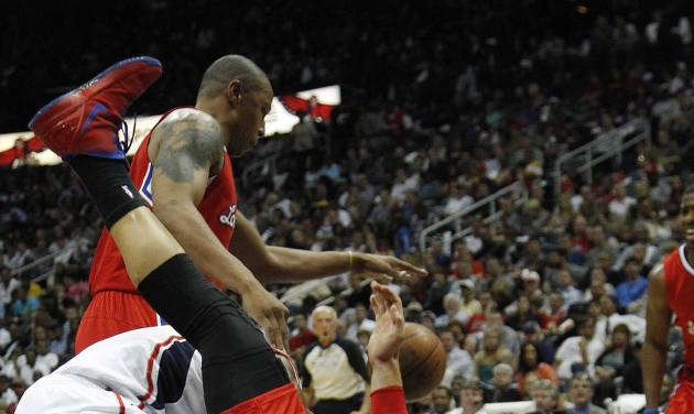Atlanta Hawks shooting guard Joe Johnson, middle, is fouled by Los Angeles Clippers power forward Blake Griffin (32) during the first half of an NBA basketball game Tuesday, April 24, 2012 in Atlanta. (AP Photo/John Bazemore)