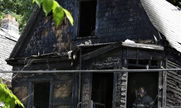 Firefighters pick through the rubble of a burned out home as they look for clues to a fire that authorities say killed six people in Newark, N.J., Sunday, June 15, 2014. The Essex County prosecutor's office says the fast-moving fire that roared through a single-family home in New Jersey's largest city, broke out at around 4 a.m. Sunday. (AP Photo/Mel Evans)