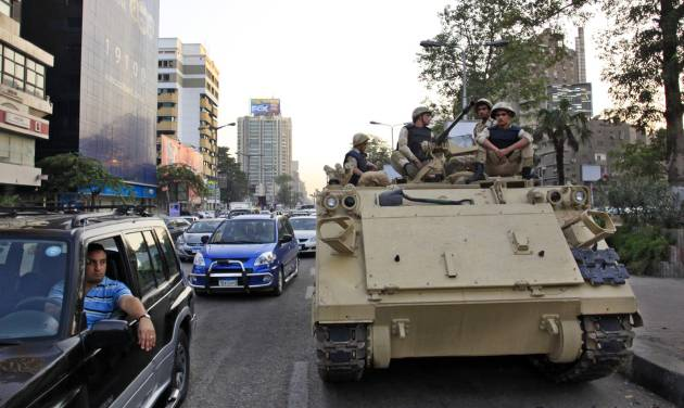 Egyptian army soldiers sit on top of an armored personnel carrier on a street in Cairo, Egypt, Saturday, Sept. 7, 2013. (AP Photo/Khalil Hamra)