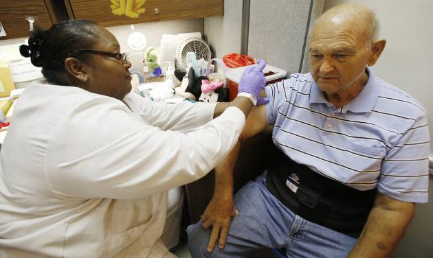 Sheri Henderson, left, gives Jerry Jackson a flu shot at the Oklahoma City-County Health Department in Oklahoma City, Friday,  October 2, 2012. Photo By Steve Gooch, The Oklahoman