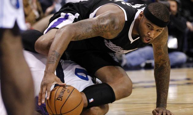 Sacramento Kings center DeMarcus Cousins, top, lands on top of Dallas Mavericks' Derek Fisher (6) chasing a loose ball in the first half of an NBA basketball game Monday, Dec. 10, 2012, in Dallas. (AP Photo/Tony Gutierrez)