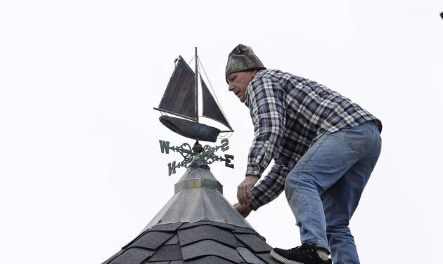 Walter Jacob stands on the peak of a roof Thursday, Feb. 7, 2013, in the Ocean Grove section of Neptune, N.J., as he works to seal the leak around a weather vane at a home damaged by Superstorm Sandy. The region is bracing for the threat of a snow storm in the next few days. (AP Photo/Mel Evans)