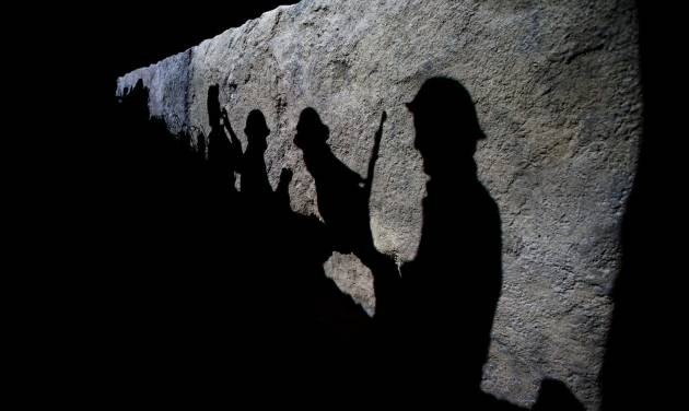 """Silhouettes of British soldiers are projected onto a trench scene in the new """"First World War Galleries"""" after major redevelopment works at the Imperial War Museum during a press preview event in London, Wednesday, July 16, 2014. The museum reopens Saturday after a six-month closure for a 40 million pound ($70 million) renovation timed to mark the centenary of World War I.  The museum was founded in 1917, as the war still raged, to preserve the stories of those who were fighting and dying. It retains that goal, as well its archaic name, relic of a long-gone British Empire.  (AP Photo/Matt Dunham)"""